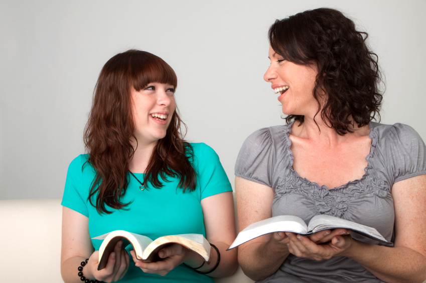 mother and teenager read together. istockphoto