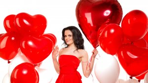 נערה עם בלוני לבבות אדומים